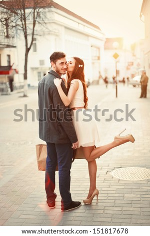 Young happy funny couple lovely posing and kissing outdoor. Handsome man have a gift for his girlfriend. Summer or autumn outdoor portrait.