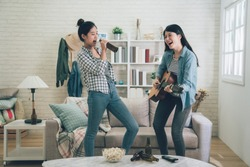 Young happy girl best friends having party one playing guitar and another singing by holding beer bottle as microphone. two asian women dancing together. Friendship leisure rest home enjoy concept
