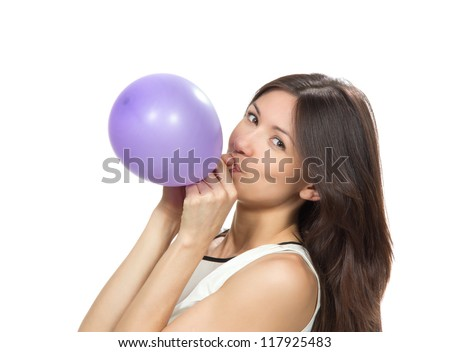 Young happy girl blowing balloons for birthday party smiling and looking at the camera on a white background