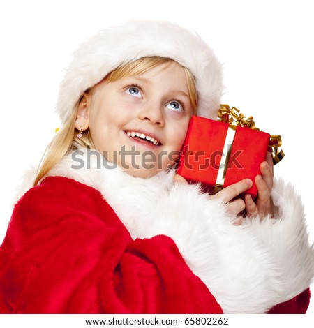 Young happy girl dressed as santa claus holds christmas gift in hands.  Isolated on white background.