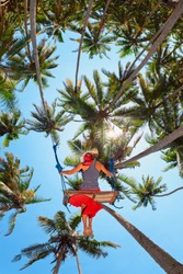 Young happy girl have fun swinging high in mid air. Flying up upside down on swing among palms on sea beach. Adventure in tropical island. Travel lifestyle, activity on summer family vacation with kid