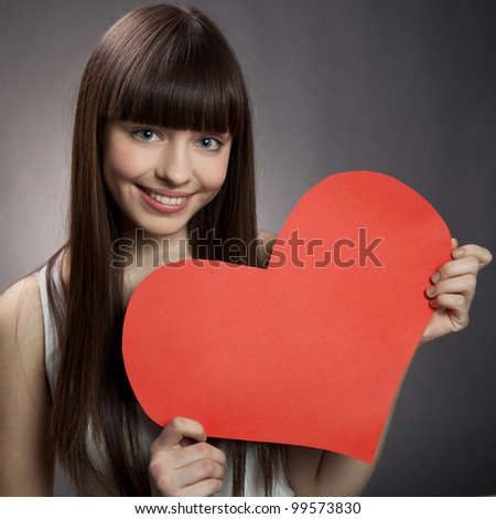 Young happy girl holding Valentines Day heart sign with copy space