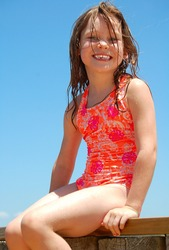 Young happy girl in bathing suit with wet hair sitting on bayside dock