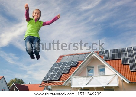 Young happy girl jumping in mid-air next to house with solar panels