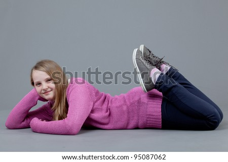 young happy girl.  little girl on a gray background