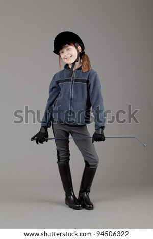 young happy girl.  little girl on a gray background. Horse and jockey - little girl.
