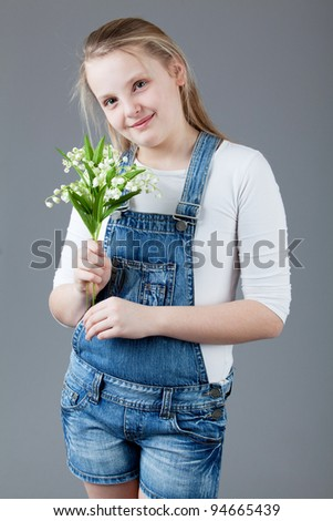 young happy girl.  little girl on a gray background. portrait of a beautiful little girl with flowers.