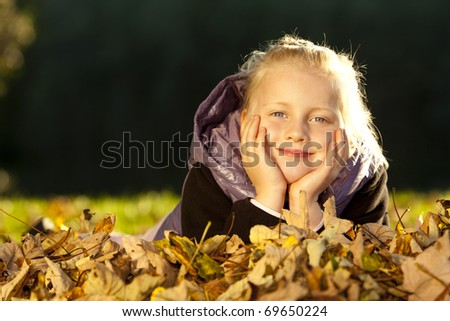 Young happy girl lying on floor in autumn leaves.