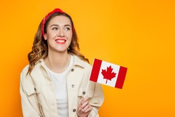 Young happy girl student smiling and holding a small canada flag and looking away isolated over orange background, Canada day, holiday, confederation anniversary, copy space