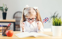 Young happy girl wears white shirt and eyeglasses learning English language with book in light stylish classroom, studying success concept