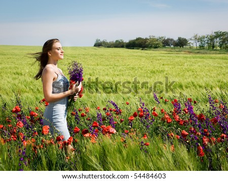 young happy girl with bouquet in wheat field
