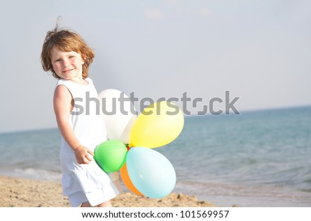 young happy girl with colorful balloons on sea background