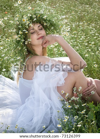 young happy girl with daisy crown on head relaxing outdoors