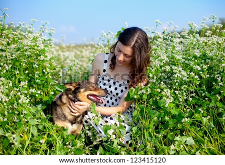 Young happy girl with dog on the buckwheat field