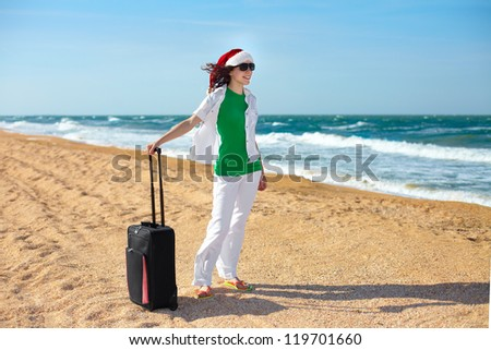 Young happy girl with traveling bag on the beach