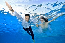 Young happy guy and girl in wedding costumes swim and pose under the water in the pool with their arms outstretched. Portrait. Concept.