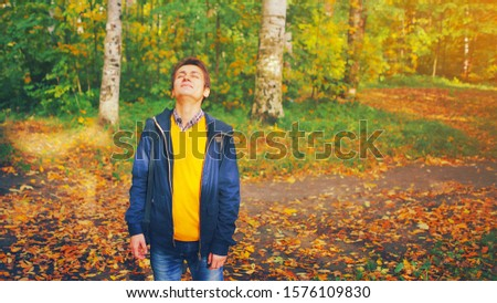 Young happy handsome man in yellow sweater and jacket in autumn park with eyes closed deep breath fresh air on sunny fall day. Concept of nature relax, people dream, wellbeing and healthy lifestyle