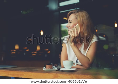 Young happy hipster girl speaking with her friend by mobile phone while relaxing in cozy coffee shop, charming lady with beautiful smile talking on cell telephone while sitting in cafe during lunch