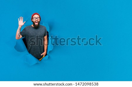 Young happy hipster guy looking through hole in paper. Crazy emotions. Copy space for your text or slogan. Discount, sale, season sales. Black friday.