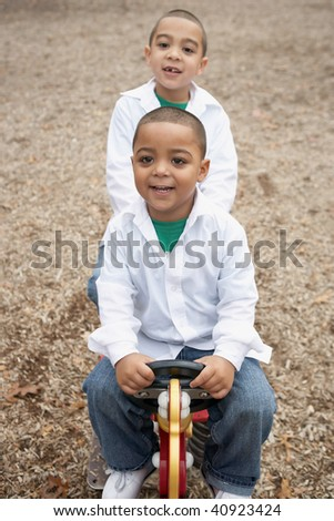 Young happy hispanic boys playing at school playground