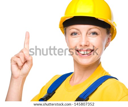 Young happy lady as a construction worker is pointing up with her forefinger, isolated over white