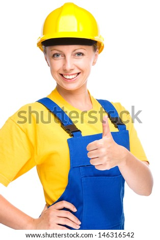 Young happy lady as a construction worker is showing thumb up sign, isolated over white