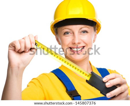 Young happy lady as a construction worker with tape measure, isolated over white