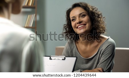 Young happy lady talking with psychologist at clinic, session of rehab therapy