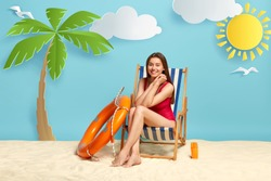 Young happy lady wears red bikini, relaxes in deckchair at beach during hot sunny day, enjoys sea vacation, smiles gladfully, uses lifebuoy and sunscreen. People, summer, travel and recreation concept