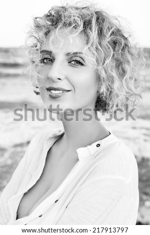 Young happy laughing girl on the beach. Black and white portrait.