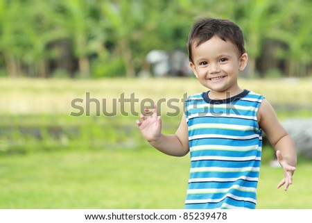 Young happy little boy smiling greeting someone in the park