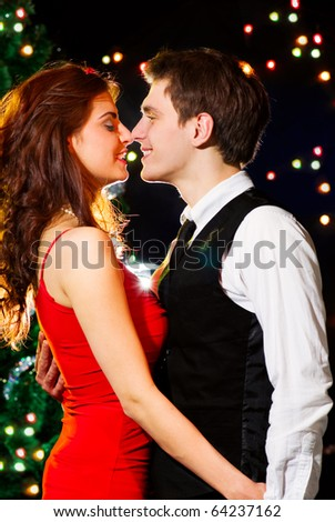 Young happy loving couple dancing at Christmas celebration near New Year's tree