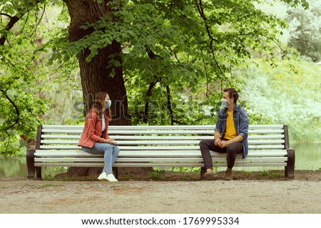 Young, happy, loving couple having date in the park during the coronavirus lockdown crisis. Relations, friendship and love concept. Social distancing and virus protection.