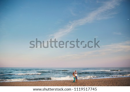 Young happy loving family hugging at beach together near the oce