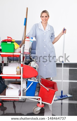 Young Happy Maid Cleaning The Floor With Mop