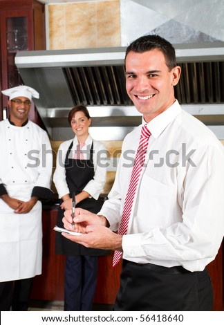 young happy male restaurant manager and his staff in kitchen