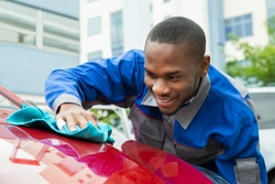 Young Happy Male Worker Cleaning Red Car With Cloth
