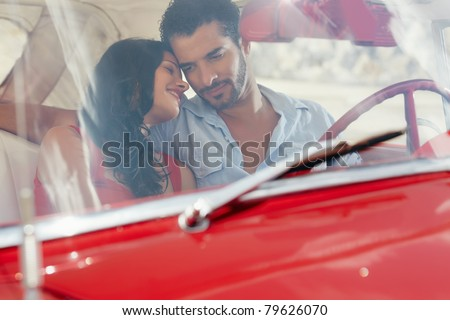young happy man and woman dating in red convertible vintage car from the 50s in havana, cuba. Horizontal shape