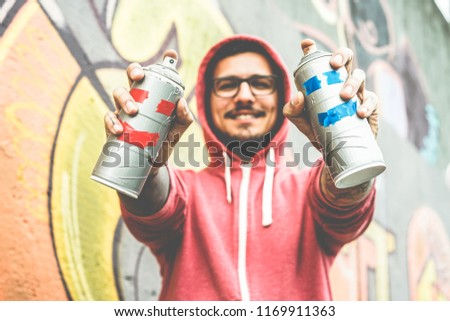 Young happy man drawing with two smiling sprays  - Graffiti artist painting with aerosol color cans on the wall - Urban lifestyle, youth, millennial generation and street art concept - Focus on bottle