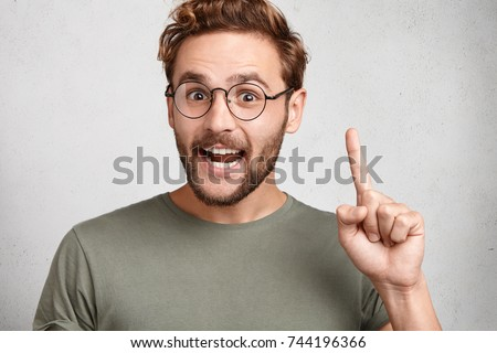 Young happy man gets good idea, raises fore finger as going to voice it, being glad have genius thoughts in mind, isolated over white background. Clever scientists understands how develop new theory