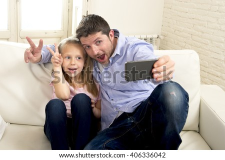 young happy man having fun with his little cute blond daughter taking selfie photo with mobile phone enjoying together at home sofa couch in father and little girl self portrait picture concept