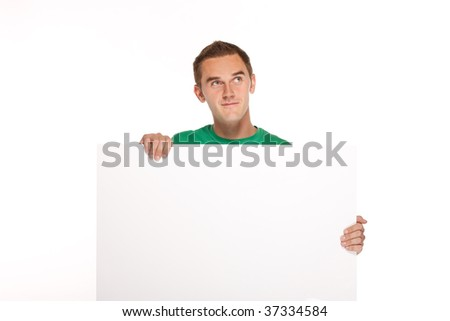 Young happy man holding a white card, good space for writing or placing an image.