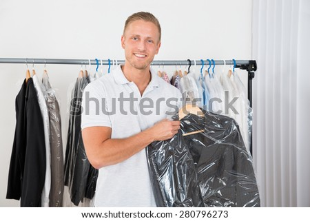 Young Happy Man Holding Coat In Dry Cleaning Store