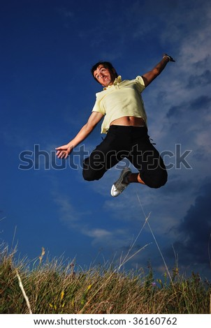 Young happy man is jumping on green meadow
