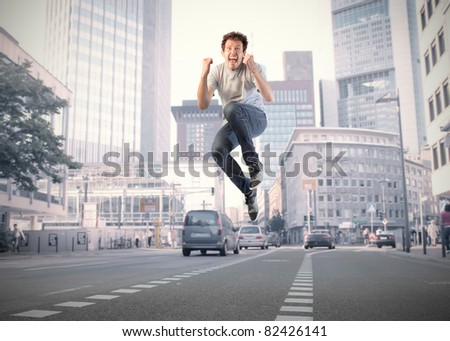 Young happy man jumping on a city street