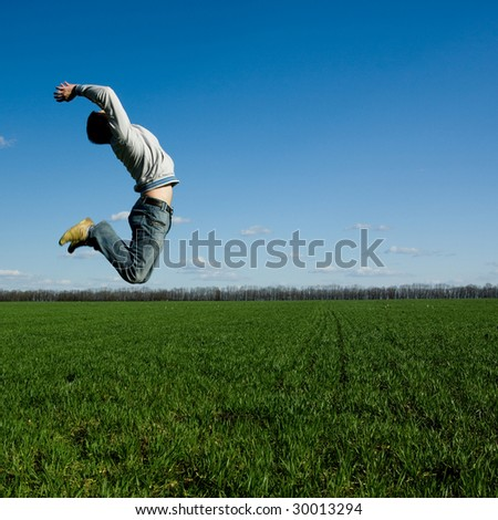young happy man jumping on the green field
