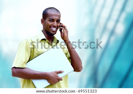 Young happy man or student with laptop and phone on the business background #69551323