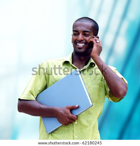 Young happy  man or student with laptop on the business background