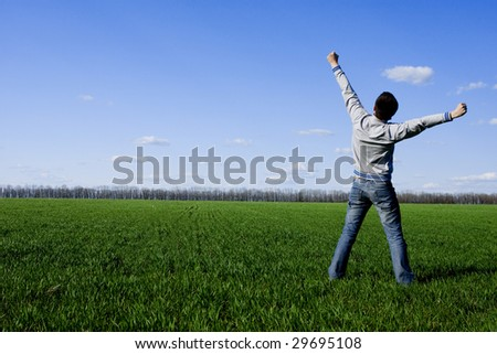 young happy man standing on the green field