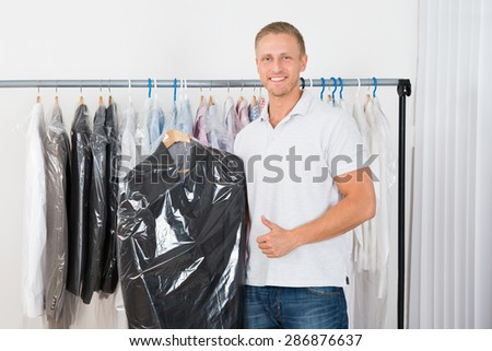 Young Happy Man Standing With Coat In Dry Cleaning Store